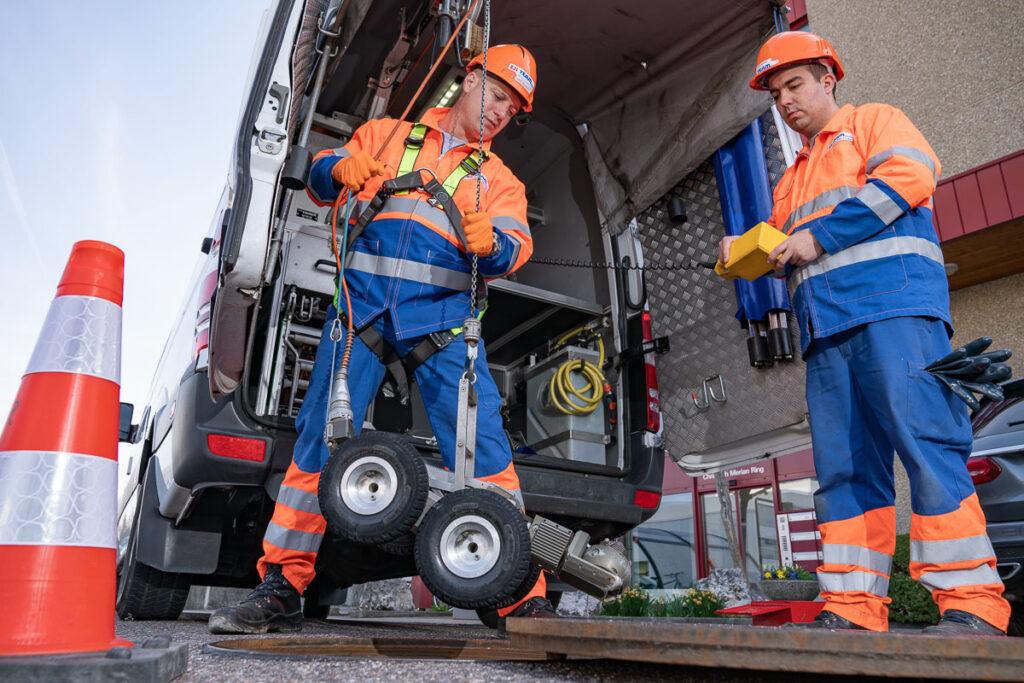 Arbeiter bei Kanalinspektion mit Kamera